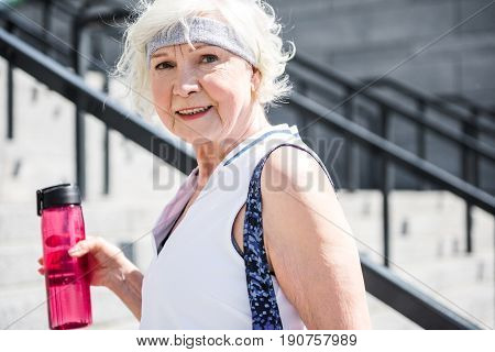 Waist up portrait of cheery old lady standing on big city ladder. She is holding bottle of water in one hand and smiling