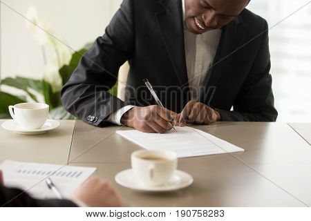Black afro american young businessman wearing suit puts signature on official document during meeting with partner, satisfied client signing contract agreement concept, making profitable deal, close up view