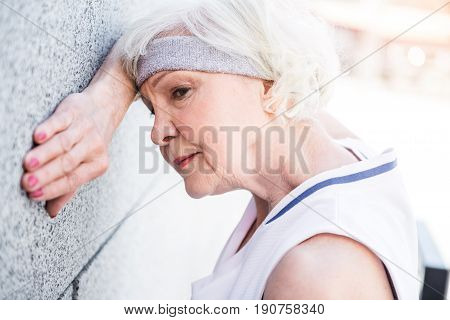 Slowly but steadily. Exhausted senior woman is leaning on wall of city building by her hand and head. She is relaxing after physical activities