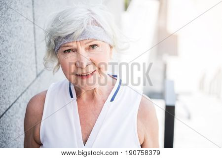 Waist up portrait of joyful senior lady standing nearby block wall. She is going to exercise outdoor. Copy space in right place