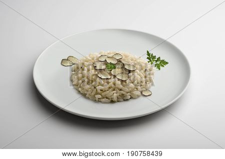 Risotto plate with small slices of truffle isolated on white table