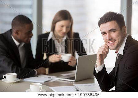 Cheerful businessman wearing suit looking at camera sitting at desk with international partners, experienced team leader holding business meeting for subordinates at background, consulting services