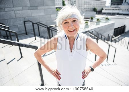 Waist up portrait of jolly old woman standing on stairs with handrails. She is keeping hands on hips and smiling