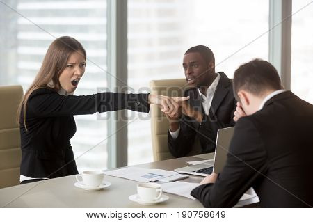 Angry female furious boss scolding employee at mixed-race team meeting, firing dismissing depressed office worker for failure, bad work results, being ineffective, pointing finger, its your fault