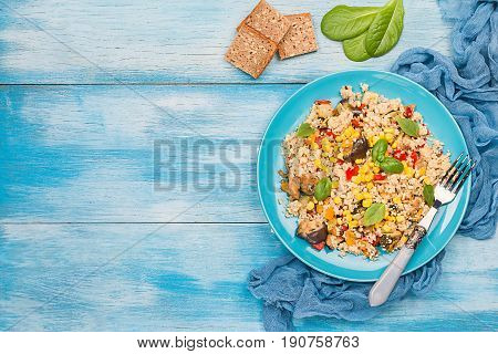 Quinoa salad with eggplant, pepper, corn, basil and tomatoes on blue plate. Superfoods concept, top view