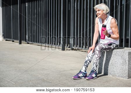 Pensive old lady is sitting on granitical block and having relax time after training. She is holding water bottle in her hand. Copy space in left side