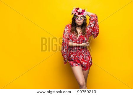 Young woman posing in flower-made chaplet and sunglasses on the yellow background.