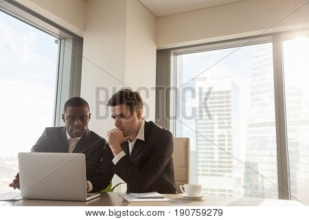 Two serious black and white businessmen discussing project sitting at office desk, using pc laptop, looking at screen, make presentation, create business plan, fulfill task, consider investment
