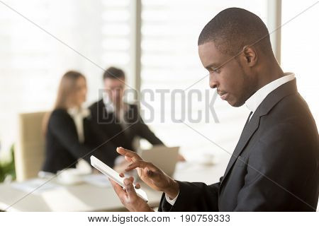 Side view portrait of afro american businessman holding smartphone or tablet with colleagues at background, useful business applications for daily work tasks, mobile payment, videoconferencing app