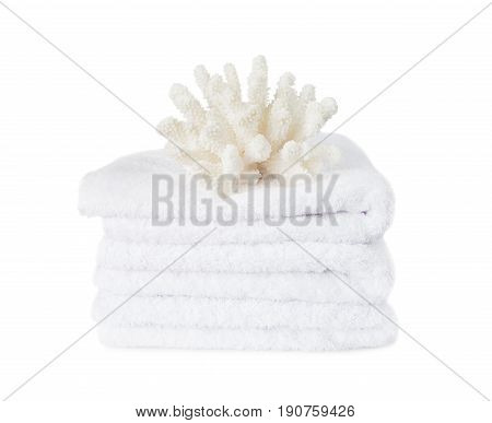 Beautiful large white coral on the stack of white fluffy terry towels isolated on a white background
