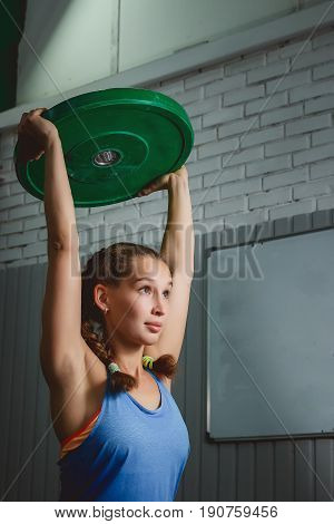 Muscular young fitness woman lifting a weight crossfit in the gym. Crossfit woman. Crossfit style.