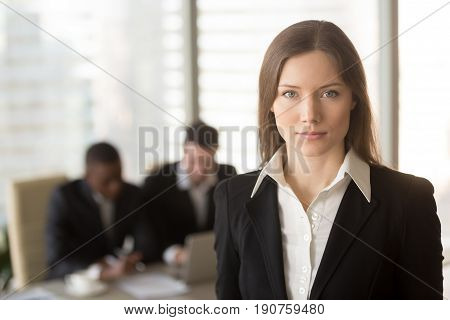 Portrait of serious attractive businesslady in office interior with male colleagues at the background, looking at camera, ambitious motivated career woman, successful female boss running own business