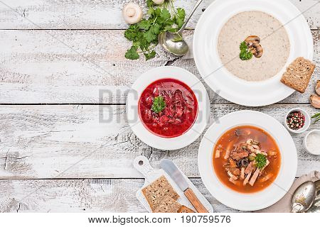 Set of three bowls with different soups: meat soup solyanka, Russian borsh and mushroom cream soup on white wooden background, top biew.