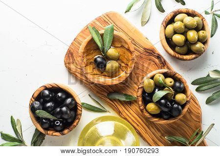 Black and green olives in wooden bowls and olive oil bottle on white background. Top view copy space.
