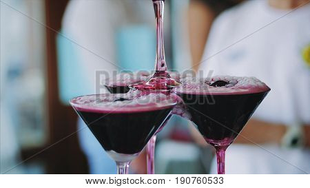The waiter in a white shirt pours wine into the pyramid from the glasses. The wine in the glasses foams and hisses - a lot of the former steam and small sprays. Young people pour sparkling wine into glasses arranged in the form of a pyramid. The smoke spr