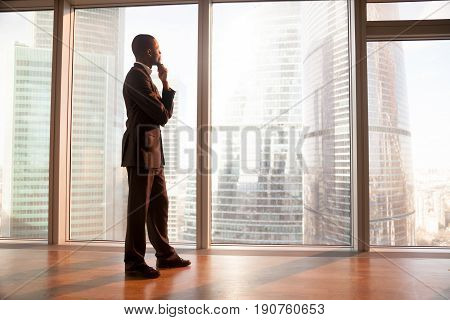 Young afro american contemplative businessman stands in office with hand on chin, looks through big window at the city, african entrepreneur enjoys sunset, rests after work, gets business inspiration