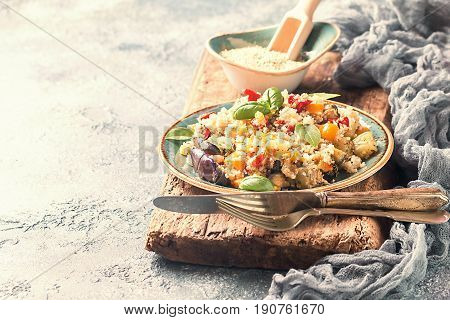 Quinoa salad with eggplant, pepper, corn, basil and tomatoes on rustic background. Superfoods concept.