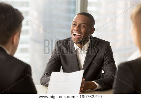 Happy black successful candidate getting hired, cheerful african applicant with beaming smile got a dream job in big company, dark-skinned businessman excited by great news, startupper found investor