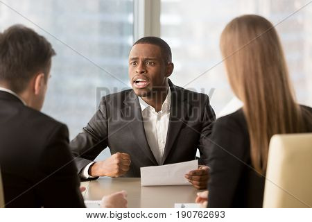 Dissatisfied african-american boss clenching fist, scolding employees for bad work, displeased team leader holding report arguing with subordinates, defrauded cheated investor demanding money back