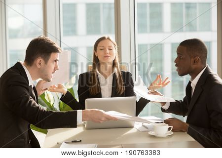 Attractive businesswoman enjoys meditating during meeting, sitting at office desk with eyes closed near arguing multiracial workers, think positive, keep calm, no stress, peace of mind, comfort zone