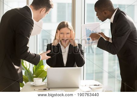 Desperate young businesswoman unable to cope with too much work, suffering stress, overworked employee looking at camera and screaming, multitasking female boss missing deadline, nervous breakdown