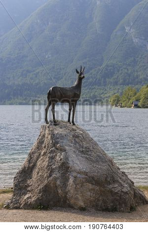Bohinj, Slovenia - June 2, 2017: Gold Horned Chamois Statue With Bohinj Lake In Background, Slovenia