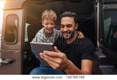 Father And Son Having Fun On Road Trip With Digital Tablet
