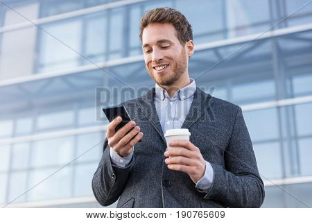 Business man looking at phone texting sms message text drinking coffee on morning break at work office. Businessman lifestyle.