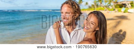 Healthy lifestyle vacation couple banner relaxing on beach honeymoon travel. Interracial young people in love at sunset. Panorama with copy space.