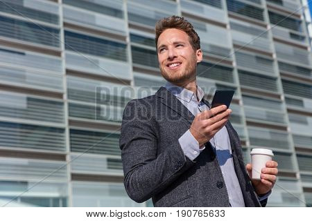 Office work man looking away businessman holding mobile cell phone. Young urban professional man using smartphone at office building. Career job opportunity concept