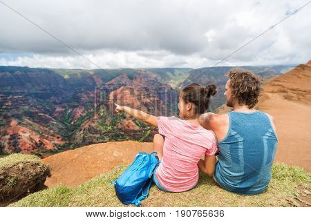 People hiking in Hawaii hikers pointing at Kauai. happy hiker couple healthy lifestyle outdoors looking at Waimea canyon view. Young couple resting sitting in nature in Kauai, Hawaii, USA.