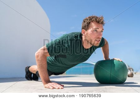 Pushup bodybuilder athlete strength training chest and shoulder muscles doing single arm medicine ball push-ups floor exercises at outdoor gym.