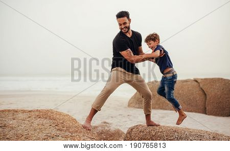 Father And Son Playing On The Rocky Sea Shore