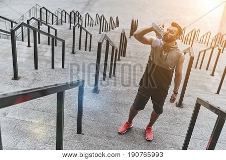 Thirsty after a run. Handsome young man in sport clothing drinking water while standing on the steps outside