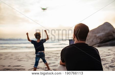 Father Operating Drone At Beach And Son Cheering