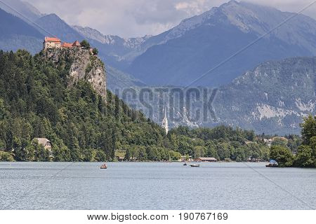 Bled, Slovenia - June 3, 2017: Tourists On Small Boats In Lake Bled With Bled Castle On Background.