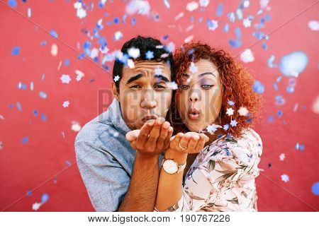 Happy Young Couple Blowing Confetti In Celebration Of Their Love
