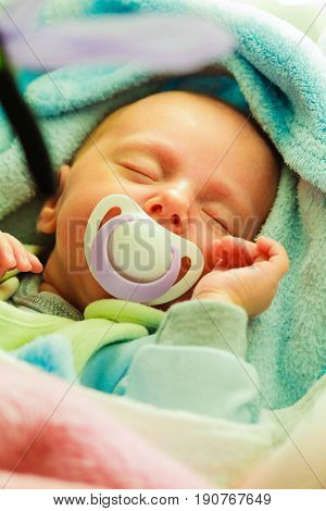 Little newborn baby in pyjamas lying on back and sleeping in bedding dummy in mouth. Family parenthood childhood concept.