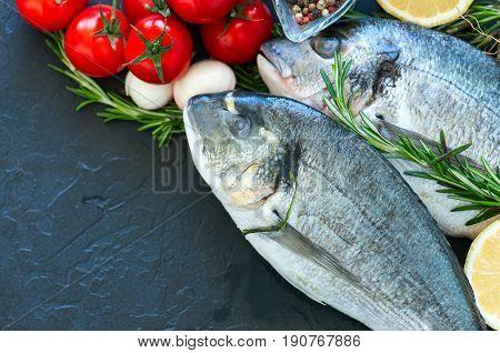 Fresh Raw Dorado Fish With Rosemary, Garlic, Tomatoes, Pepper And Lemon On A Black Slate Background.