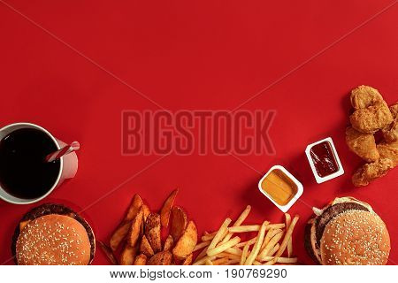 Burger and Chips. Hamburger and french fries in red paper box. Fast food on red background. Hamburger with tomato sauce. Top view, flat lay with copyspace