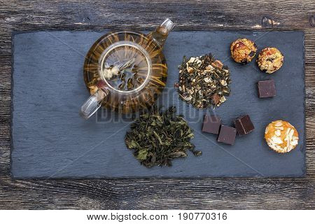 Green tea with cake, dried fruits and chocolate on wooden table
