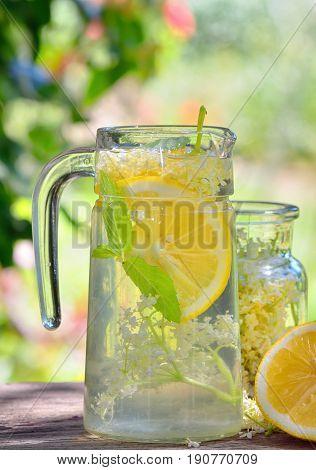 Elder lemonade with lemon on old table wood
