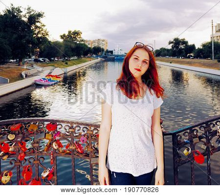 Ginger hair woman standing on the bridge of love with many locks hanging on the barrier.