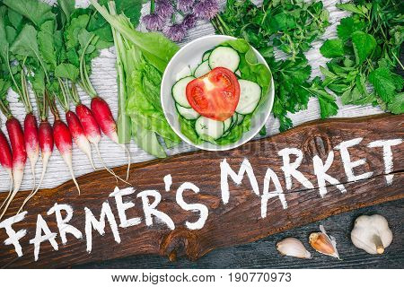 Wooden board with handwritten text 'Farmers market' and variety of fresh vegetable such as tomato, cucumber, raddish, salad, cilantro, oregano and garlic on wood background. Flat lay