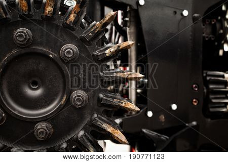 Forest harvester machine black metal circular saw close-up background. Heavy forestry vehicle for wood harvesting industrial backdrop