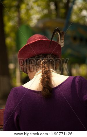 Khabarovsk Russia - June 11 2017: Young Caucasian woman wearing historical costume - felt purple dress and red Tirol hat with feathers. Beautiful lady back view at medieval reenactment in a forest
