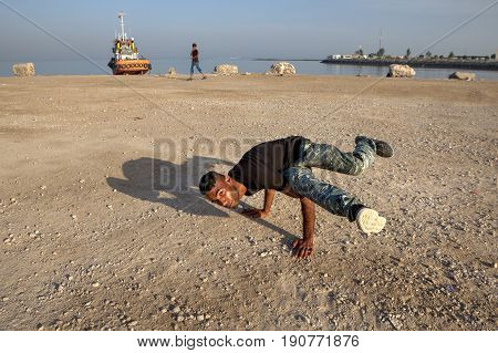 Bandar Abbas Hormozgan Province Iran - 16 april 2017: The Iranian young man shows a figure a breakdance on the beach of the Persian Gulf.