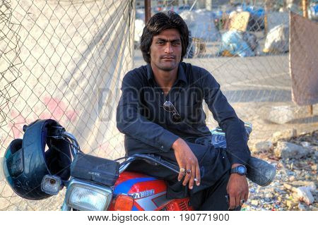 Bandar Abbas Hormozgan Province Iran - 16 april 2017: A portrait of an Afghan man who is resting in the shadows sitting on the saddle of his motorcycle.