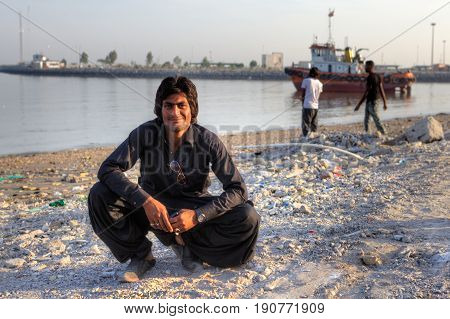 Bandar Abbas Hormozgan Province Iran - 16 april 2017: Portrait of a smiling afghan man resting on a Persian gulf beach on a sunny evening.