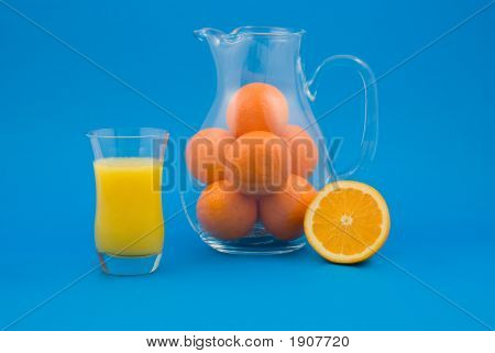 Fresh Orange Juice In Glass And Whole Oranges In Pitcher With Ha